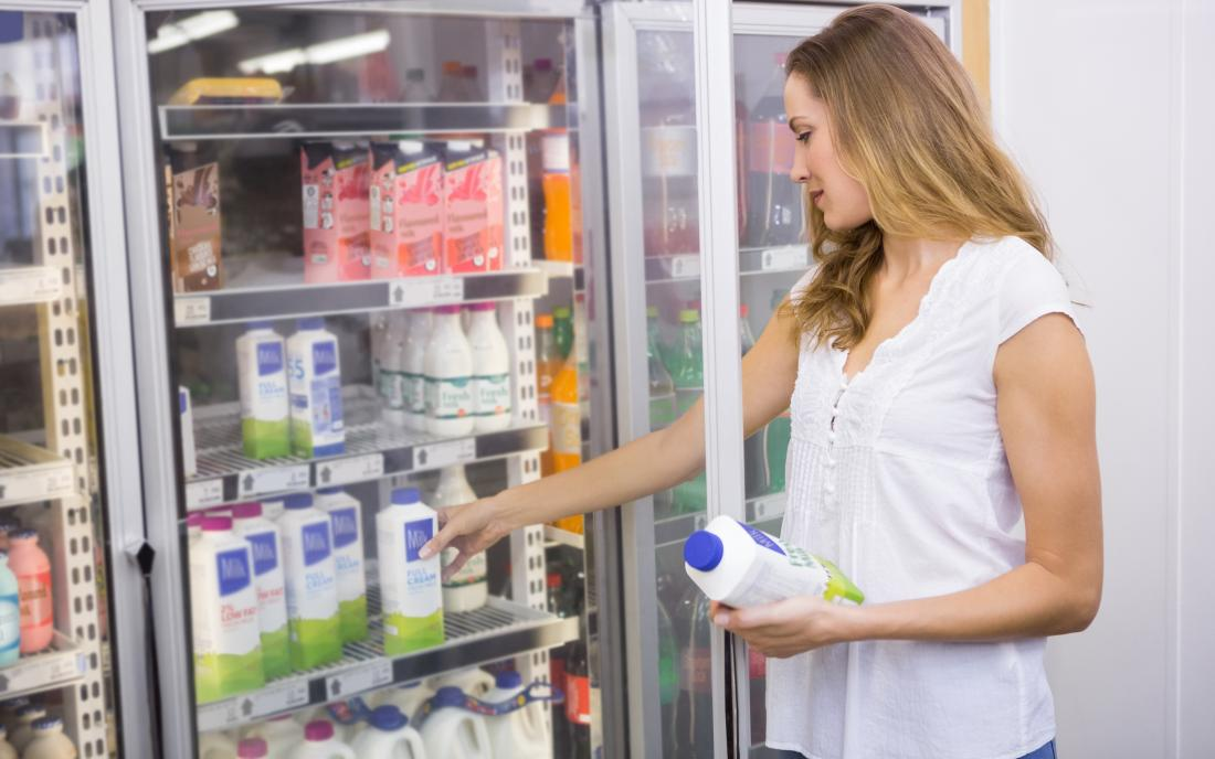 Donna in un supermercato che sceglie latte
