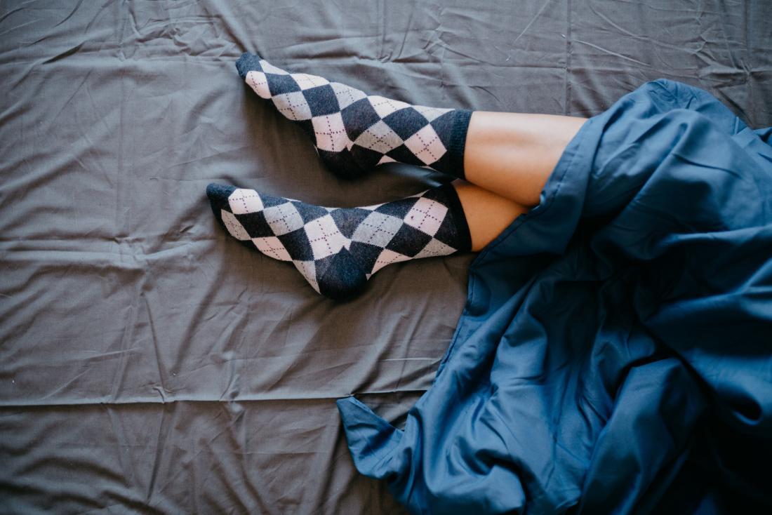 Personne sur un matelas noir et drap bleu avec les pieds qui sortent de la fin, portant des chaussettes bleues et blanches.