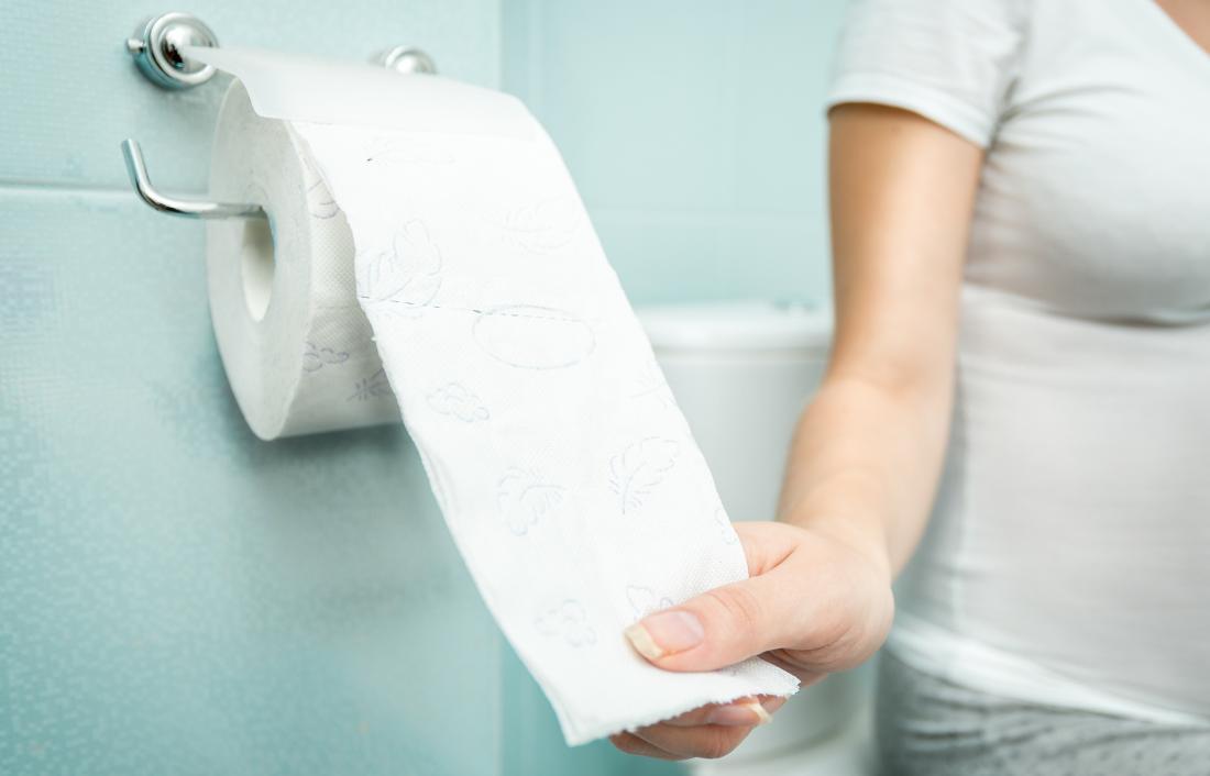 Frau greift nach Toilettenpapier wegen klebrigen Poop.