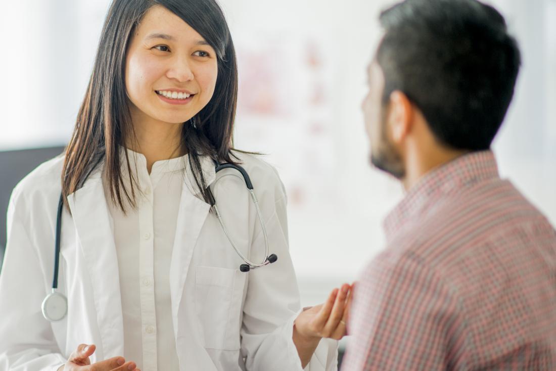 Ärztin, die mit männlichem Patienten während der Beratung spricht.