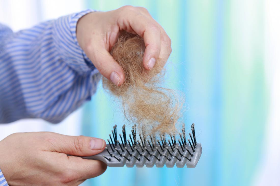 homme tirant les cheveux d'une brosse à cheveux avec effluvium télogène