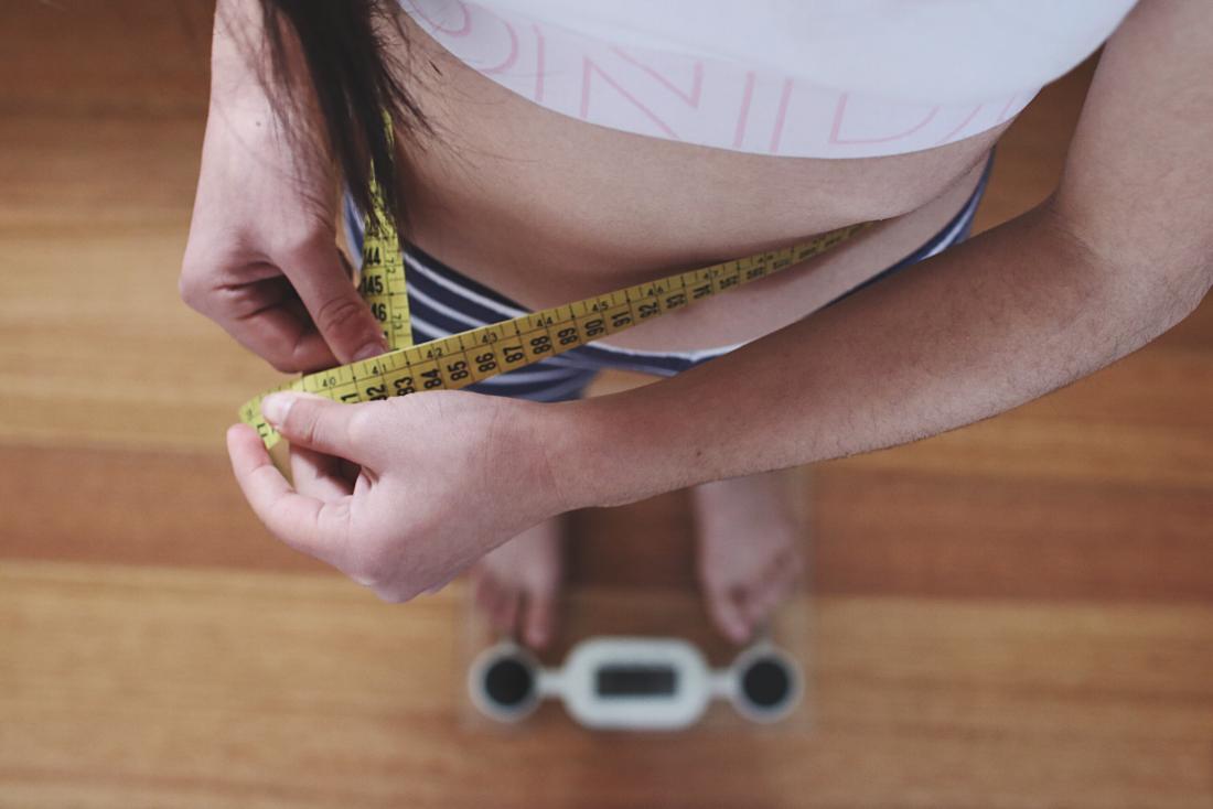 osoba na skale mierząca ich talię