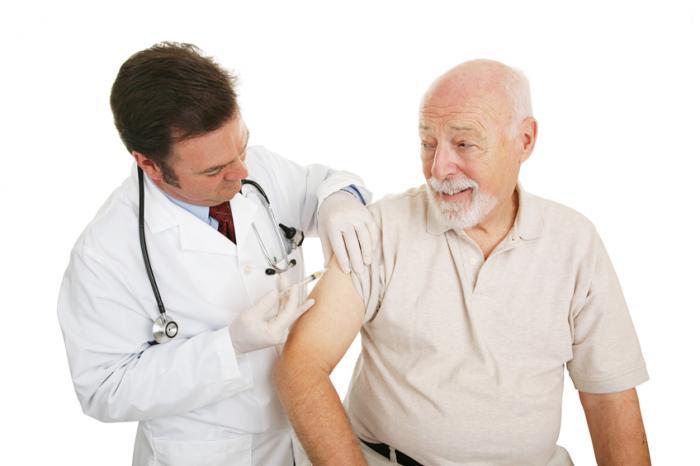 Ein älterer Mann, der einen Impfstoff hat.