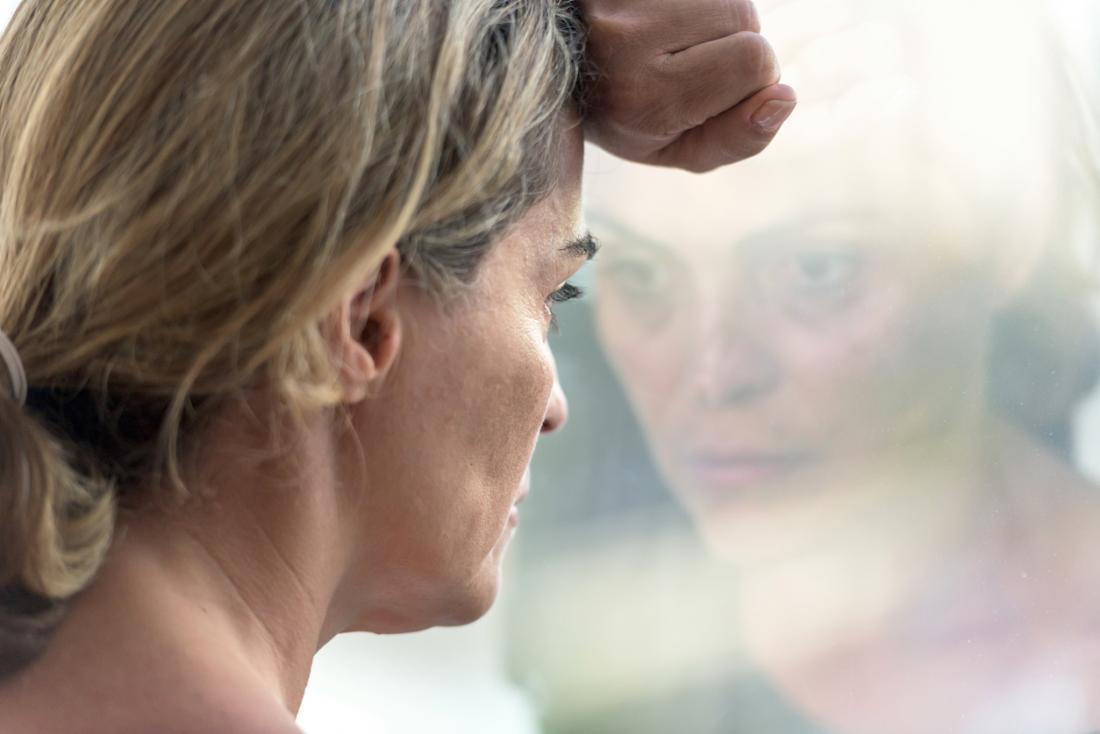 traurige Frau aus einem Fenster schauen