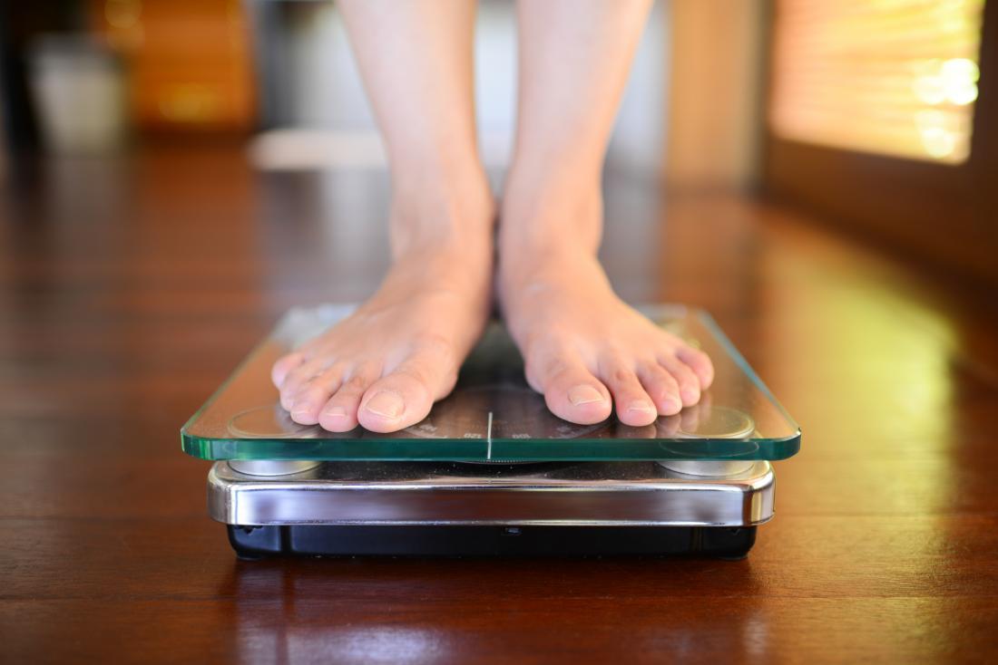 Người đàn ông đứng trên cân nặng đại diện cho trọng lượng trung bình cho nam giới.