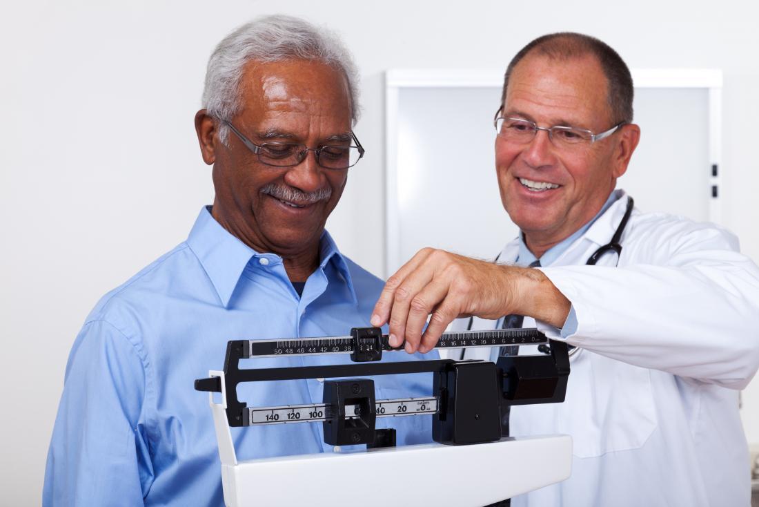 Người đàn ông trên cân nặng được đo bởi bác sĩ.