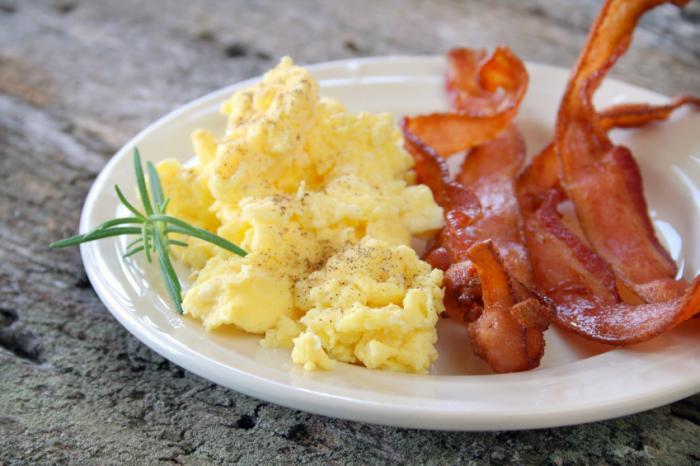 Oeufs brouillés et bacon sur assiette.