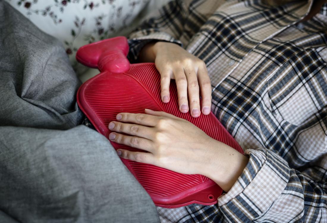Personne tenant une bouteille d'eau chaude à l'estomac en pyjama sous couverture.