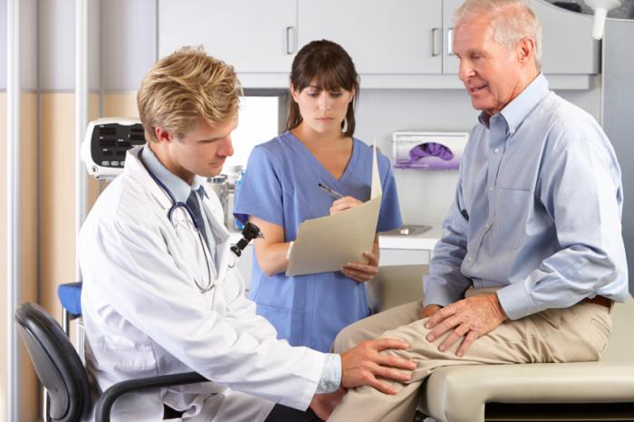 Un médecin examine le genou d'un homme plus âgé.