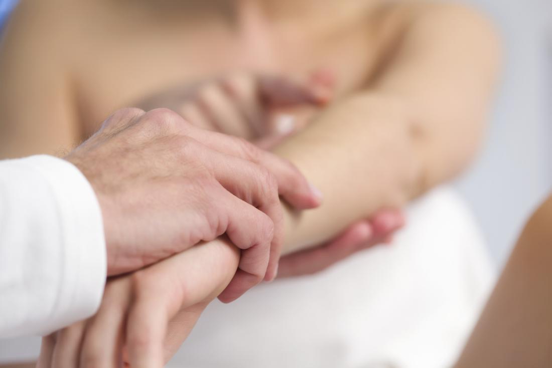 dottore guardando la pelle sul braccio di un paziente