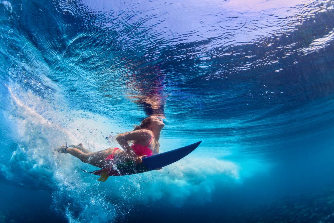 ragazza sott'acqua su una tavola da surf