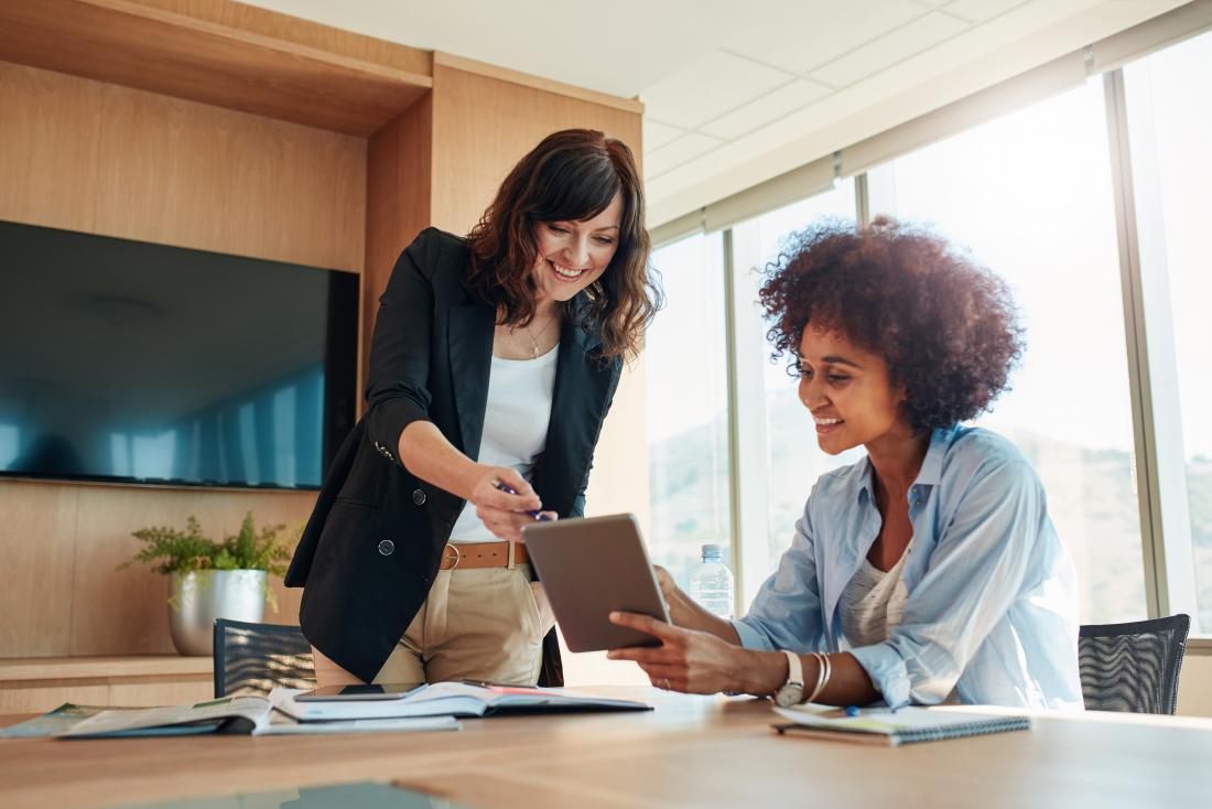 Due donne che guardano insieme un tablet in ufficio.