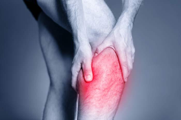 Homme tenant la jambe comme il souffre de douleurs à la jambe