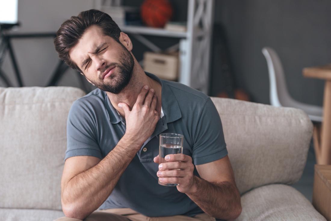 Người đàn ông bị đau họng đau, cầm một ly nước.