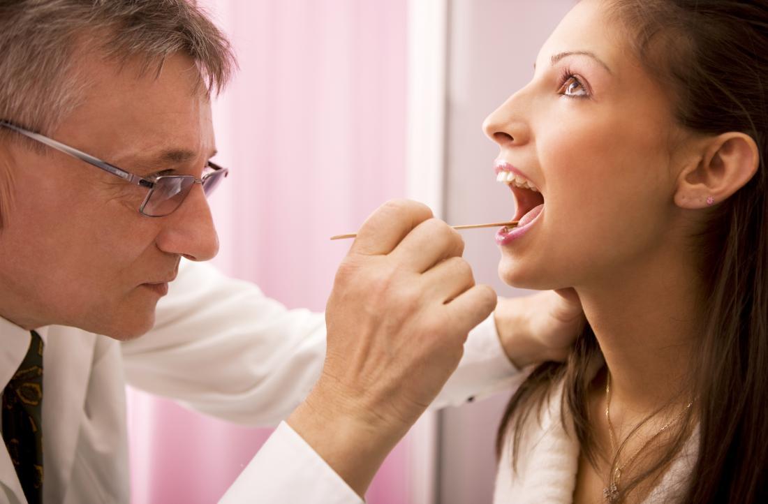 Frau, die ihre Zunge und Kehle von Doktor inspiziert hat.