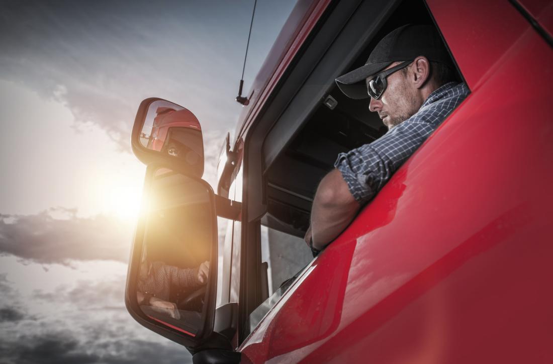 homme avec des lunettes de soleil au volant d'un camion