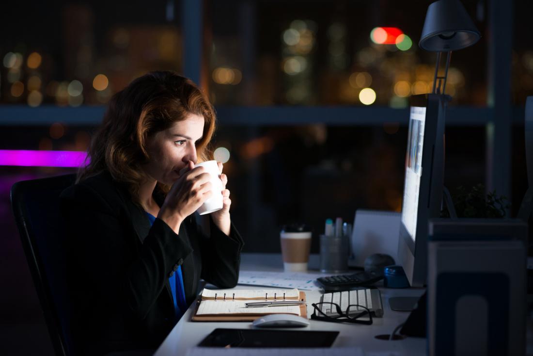 femme en sirotant un café à son bureau la nuit