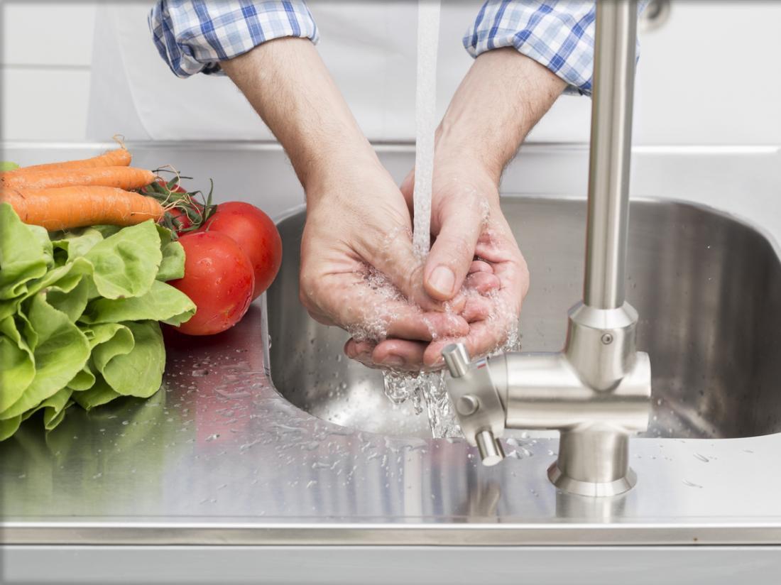 Người đàn ông rửa tay và rau trước khi nấu