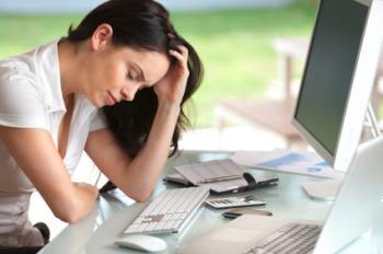 疲れた女性が机に座っている。