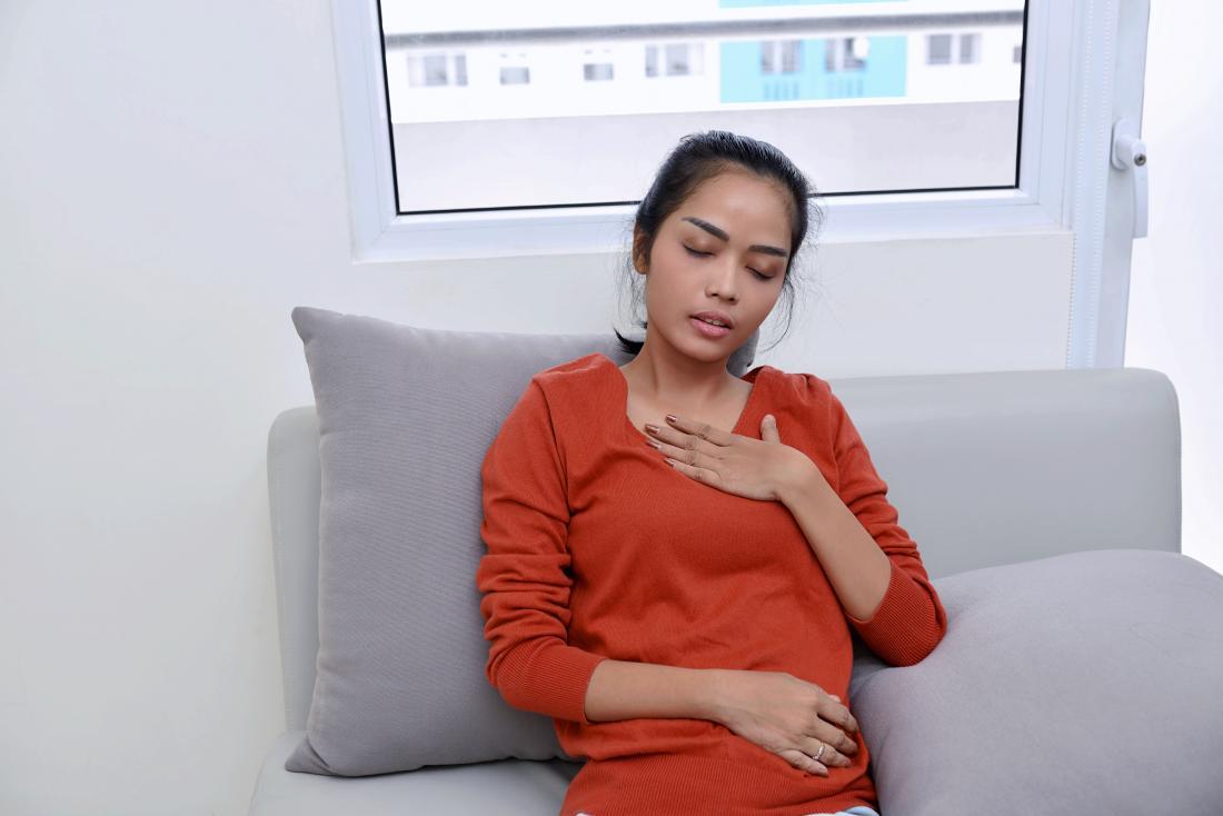 Người phụ nữ ngồi trên ghế sofa bị khó thở, cầm tay vào ngực.