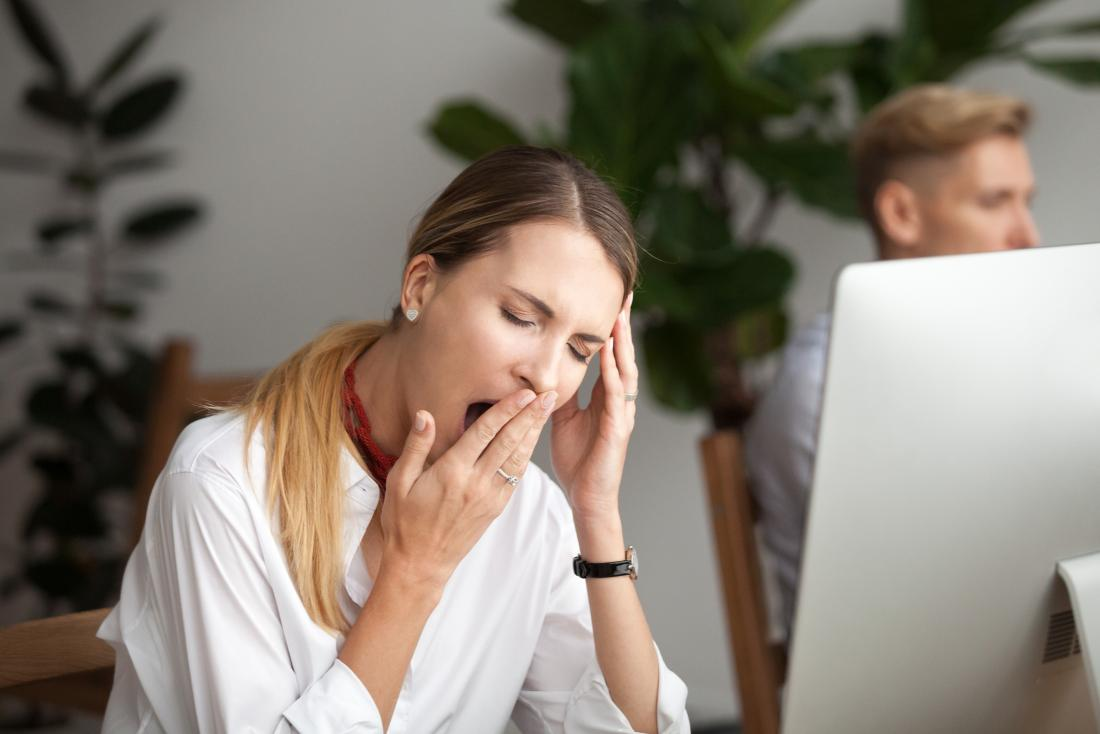 młoda kobieta ziewanie, podczas gdy przed komputerem