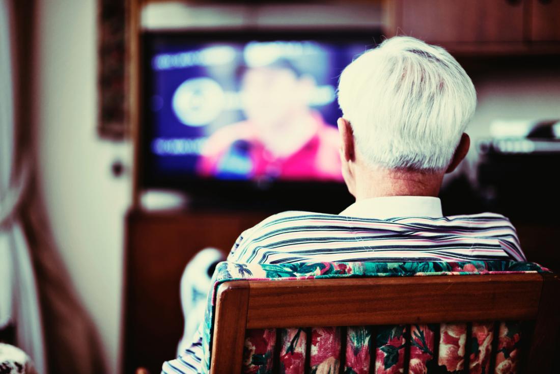 älterer Mann, der allein Fernsehen schaut