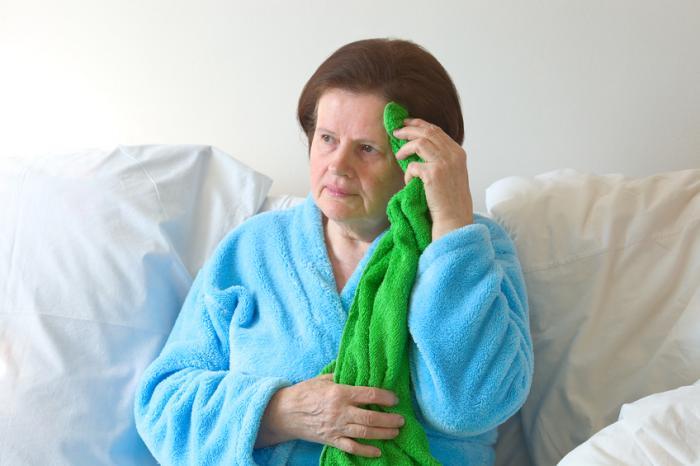 Уморена жена държи кърпа.