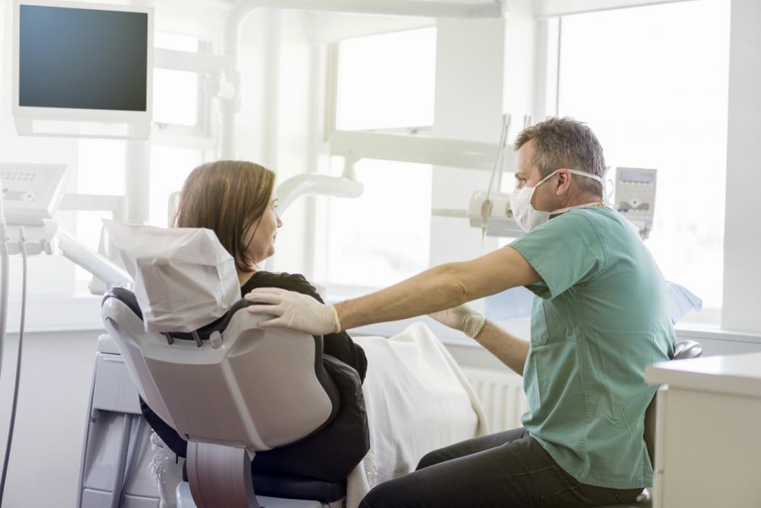 Erkek diş hekimi Bayan hasta hazırlanıyor.