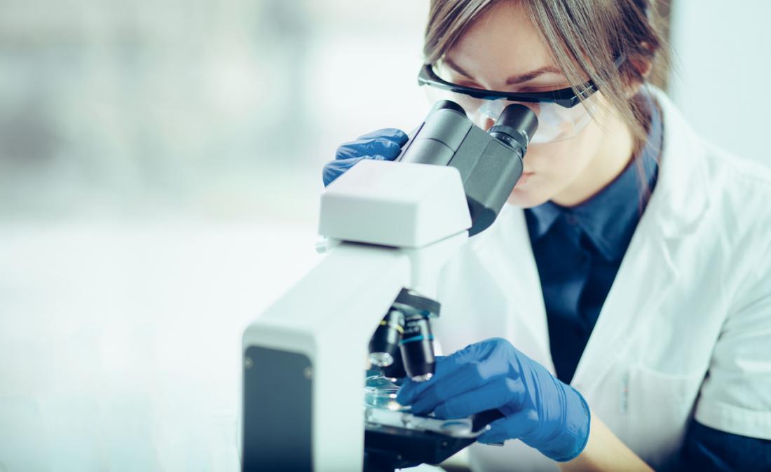Laboratuardaki genç kadın, mikroskopla bir örneğe bakıyor.