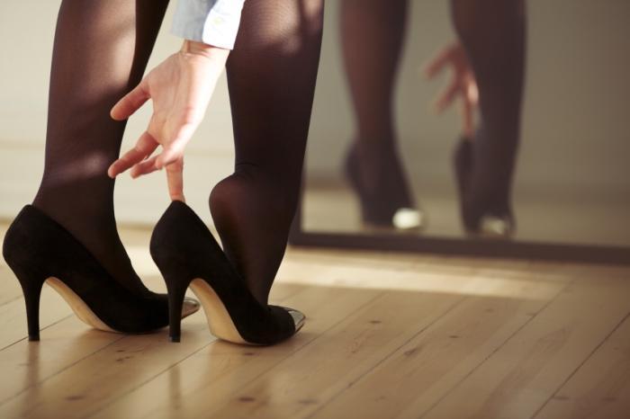 Una donna che si mette le scarpe col tacco alto