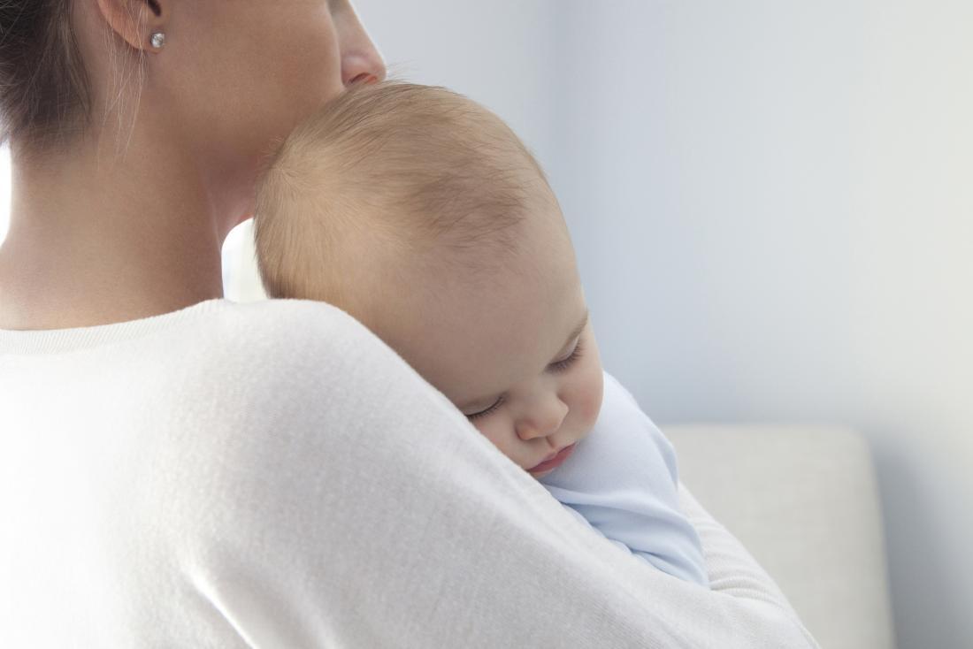 Mutter, die Baby mit Meningitis hält.