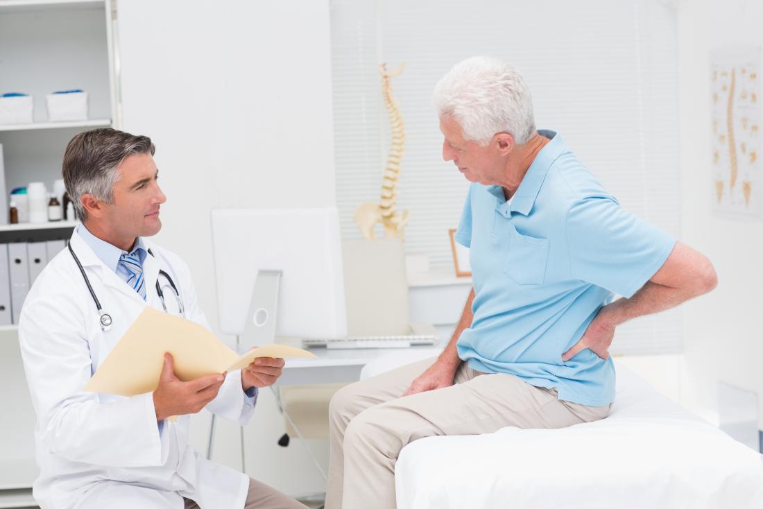 Старши човек в офиса на хиропрактиците обяснява болка в средата на гърба до лекар.