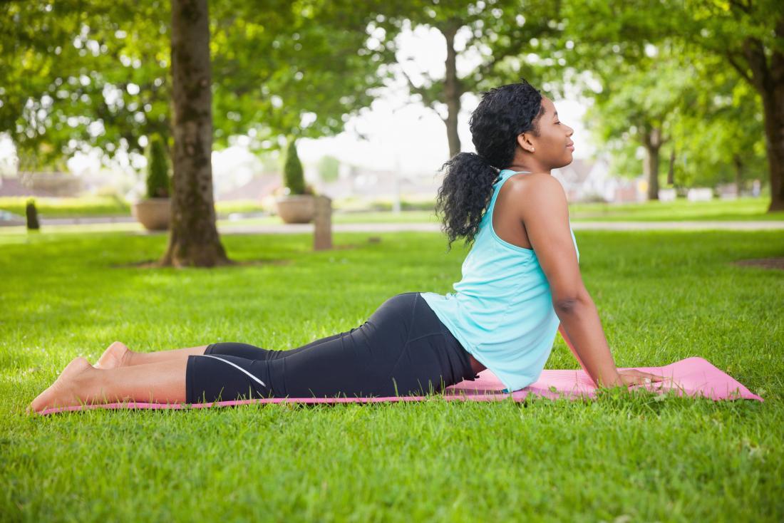 Frau draußen auf Yogamatte in der Kobrahaltung.