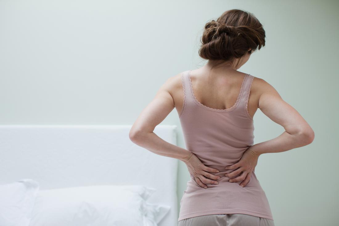 Rückenschmerzen in der Frau, die sie zurückhält.