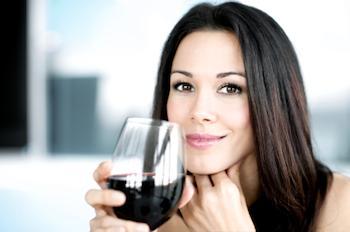Dame, die ein Glas Rotwein anhält