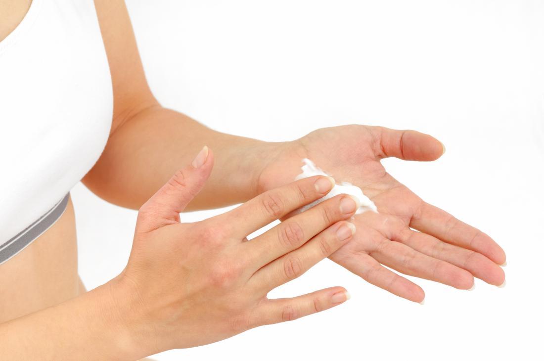 Người phụ nữ áp dụng kem dưỡng da steroid hoặc kem dưỡng da cho da.
