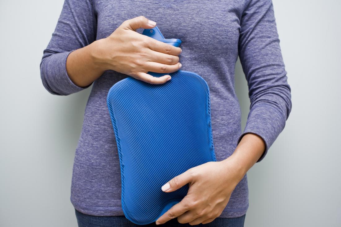 Mulher segurando uma garrafa de água quente para o abdômen.