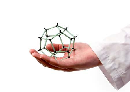 Mano di scienziato che tiene il modello molecolare della sfera di grafite