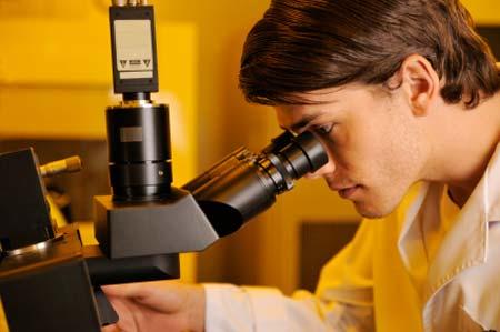 Ricercatore che lavora con uno strumento ottico in un laboratorio di nanotecnologia.