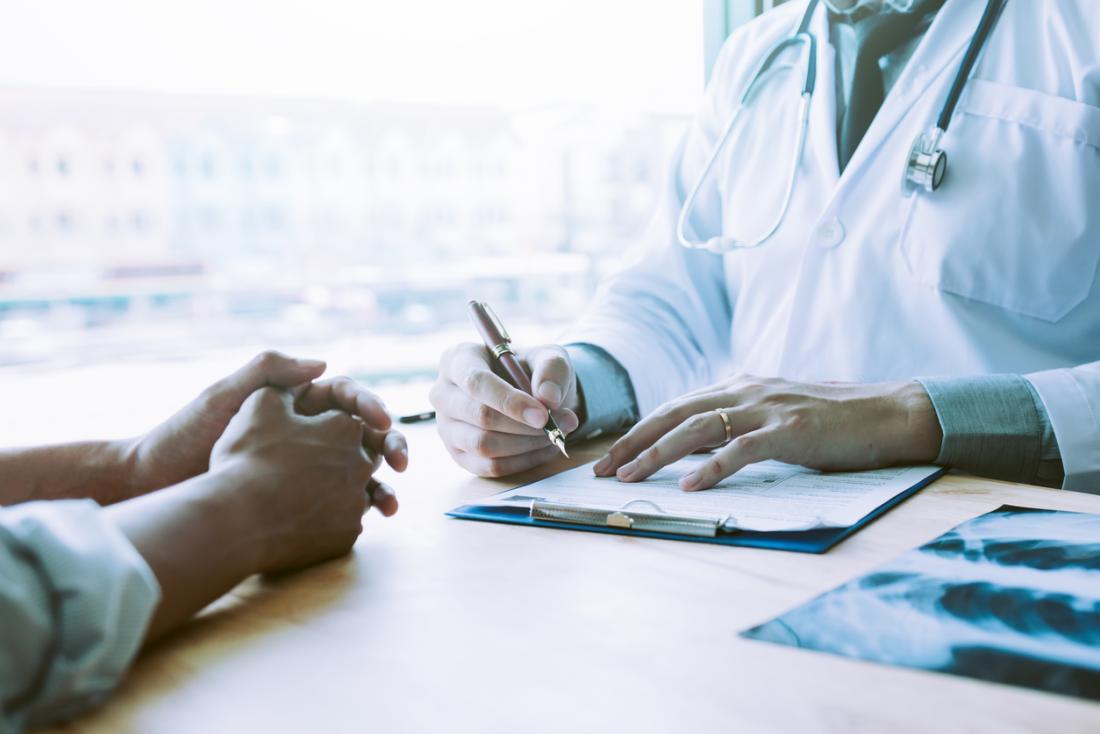лекар, който пише бележки с пациент