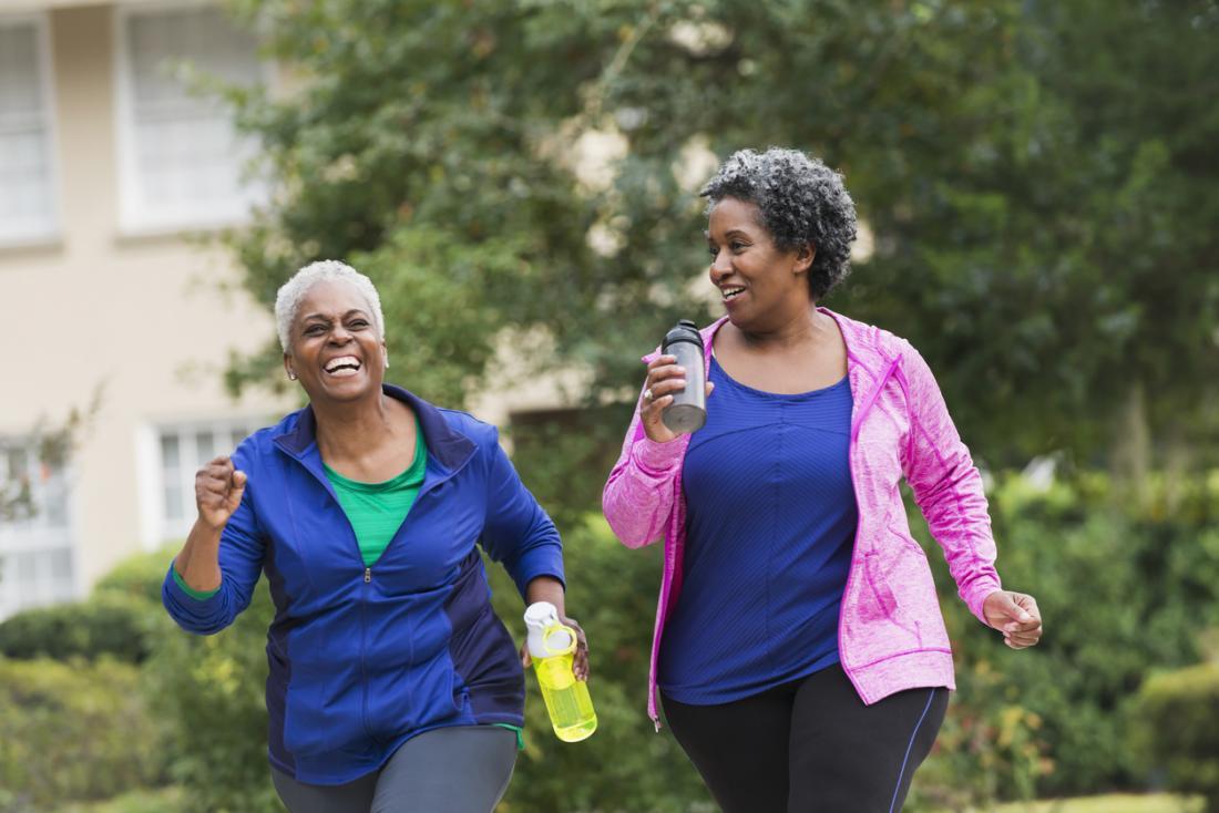[Deux femmes plus âgées qui rigolent en faisant de l'exercice à l'extérieur]