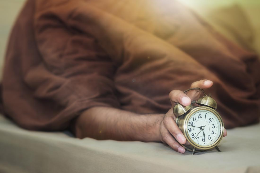 Homme endormi avec réveil
