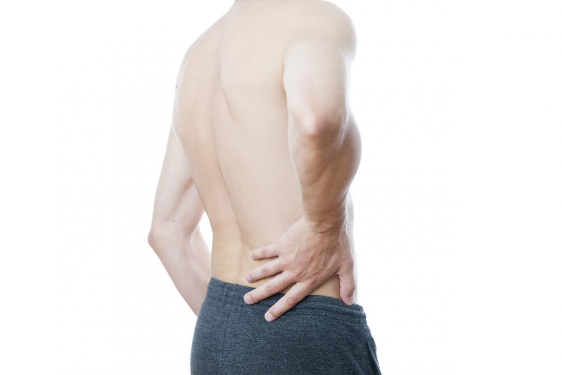 Mann hält die linke Seite seines Rückens