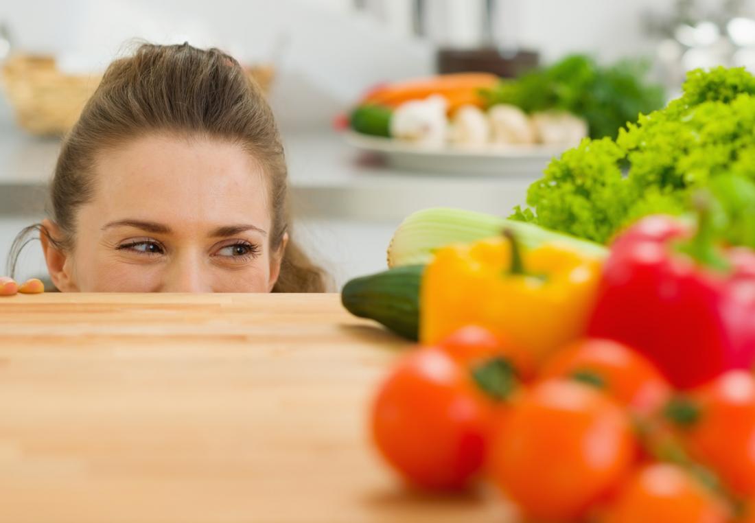 mulher olhando para legumes
