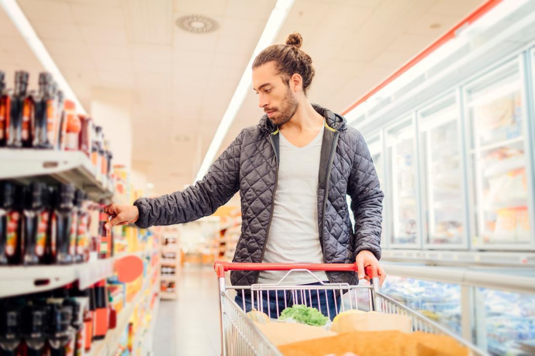 Alimentation de jeune homme, faire du shopping dans un supermarché, lire des étiquettes de produits et des informations nutritionnelles.