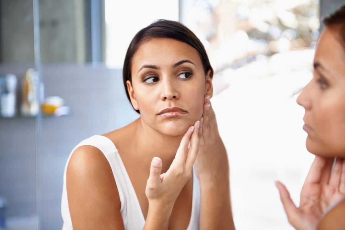 Femme vérifiant son visage dans le miroir pour des taches et des imperfections sur sa peau.