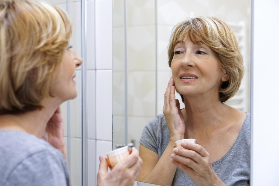 女性は、彼女の顔にモイスチャライザーを使用して、更年期発疹を助ける