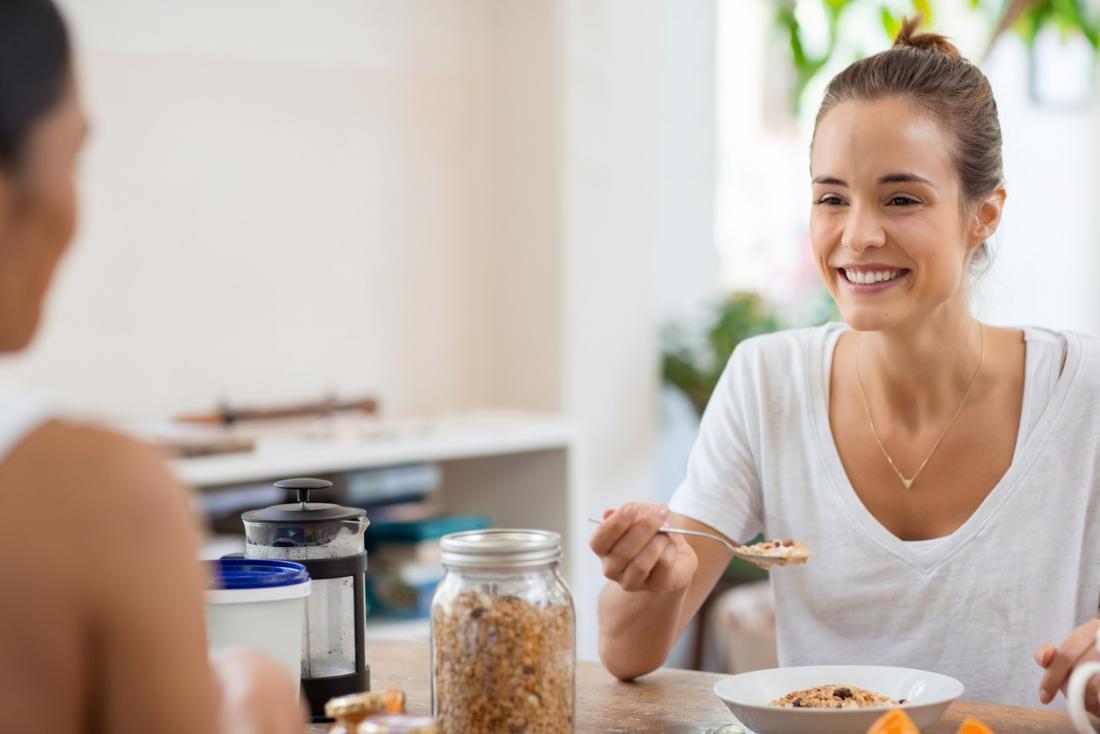 [feliz senhora comendo aveia no café da manhã]