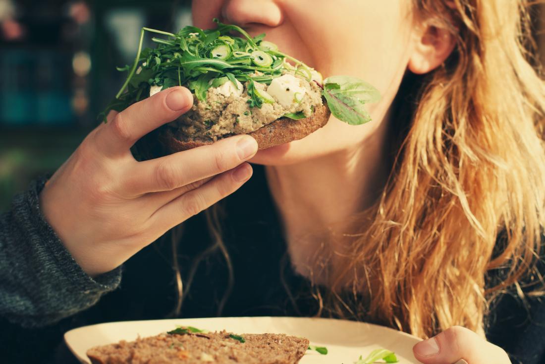 Sebzeli sandviç yiyen kadın.