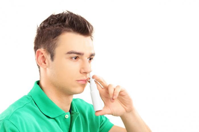 鼻スプレーを持つ男